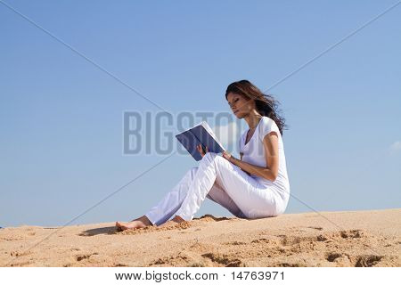 young beautiful happy arabic woman reading on beach