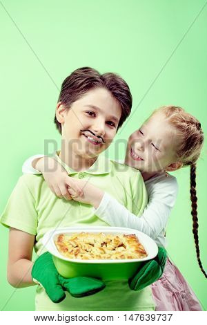 Portrait of little boy with apple pie embracing his girlfriend