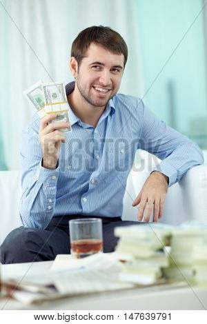 Happy man sitting on sofa and holding money