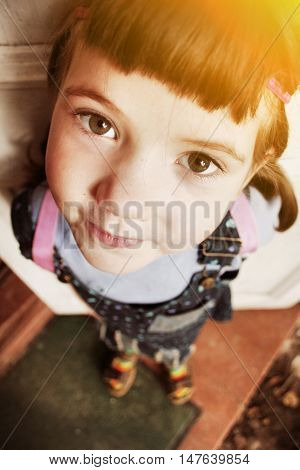 little dark hair girl foreshortening close up portrait on the country house porch mat