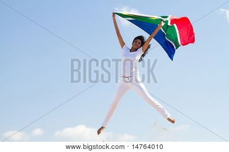 happy young woman holding a south african flag and jumping on beach