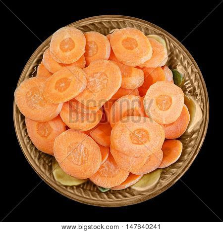 Sliced carrots in a bowl isolated on black background