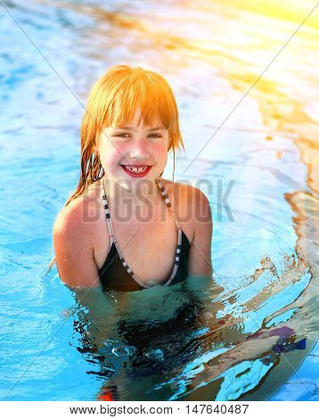 preteen smile little blond girl in outdoor swimming pool close up portrait
