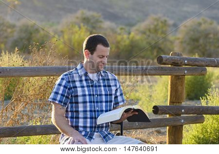 Reading the Bible outdoors with sunlit brush in the background.