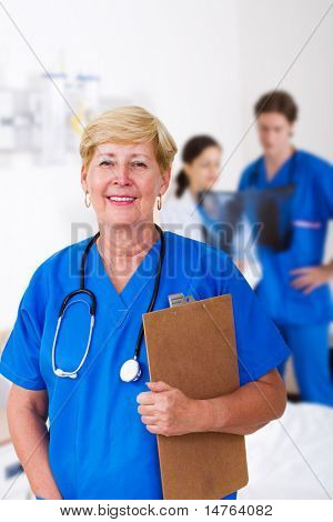 senior nurse with clipboard in hospital, background is her young colleagues