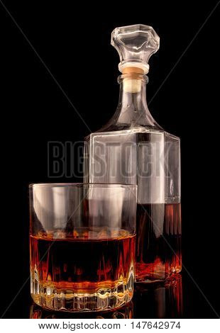 Glass and decanter with alcohol on a chyoony background with reflection. Vertical format. Glass. Indoors. Color. Photo.