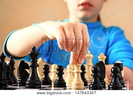 Little beautiful girl with an interest in playing chess indoors.