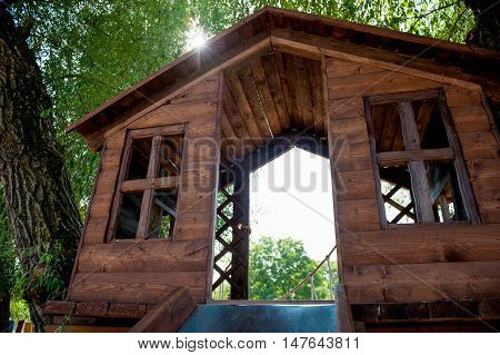 wooden house with windows on the tree on the playground