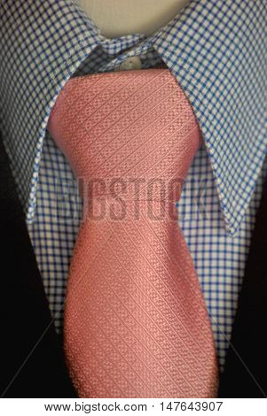 Textured pink tie with blue and white checked shirt in close-up