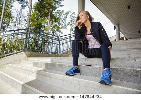 Low angle view of thoughtful young woman in sportswear sitting on steps