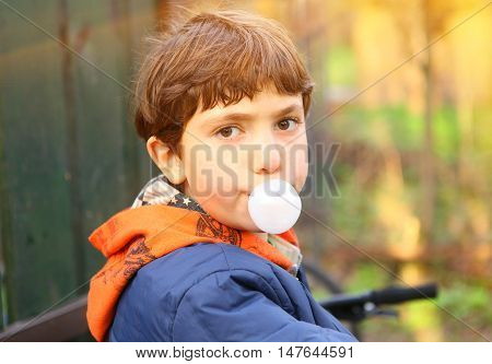 preteen handsome boy with chewing gum bubble going out country sunny close up portrait