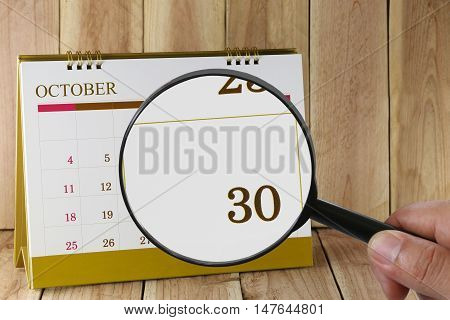 Magnifying glass in hand on calendar you can look thirtieth date of monthFocus number thirty in OctoberConcept in business and meetings.