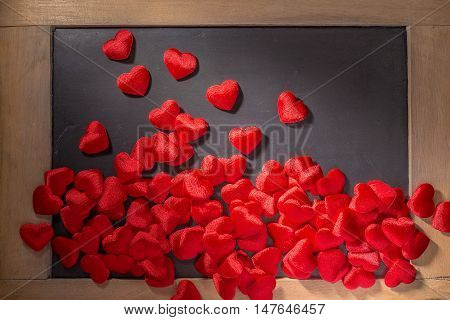 Small clothed red hearts scattered around the lower part of small chalkboard with side hard lighting