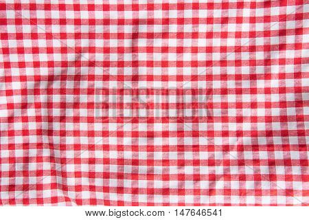 The crumpled checkered tablecloth background. Top view.