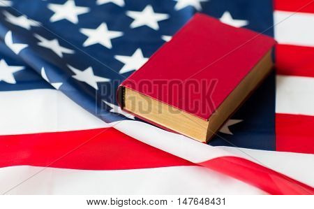 independence day, patriotism, civil rights, cultural values and nationalism concept - close up of american flag and constitution book or bible