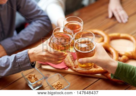 people, leisure and drinks concept - close up of male hands clinking beer glasses and pretzels at bar or pub
