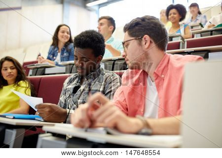 education, high school, university, learning and people concept - group of international students with test in lecture hall