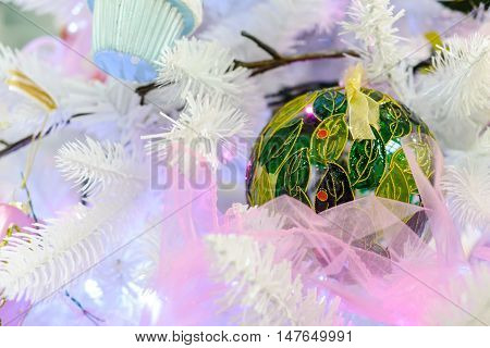 Christmas decorations on artificial fir. Christmas decorations on artificial fir. Christmas toy green ball with ornaments.