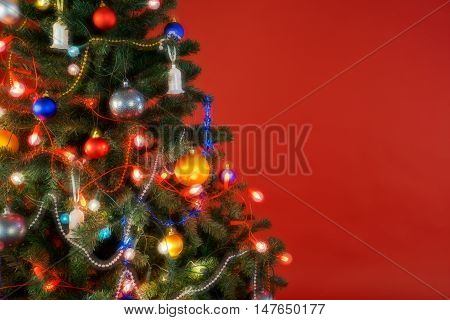 Multicolour Christmas tree with decorations and lights and red background