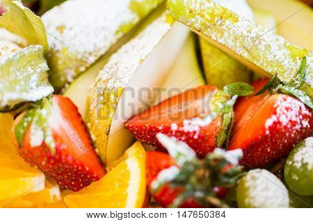 food, fruits, dessert and summer concept - close up of dish with sugared strawberries, pears and orange
