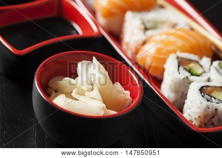 Sushi assortment on plate with chopsticks on black