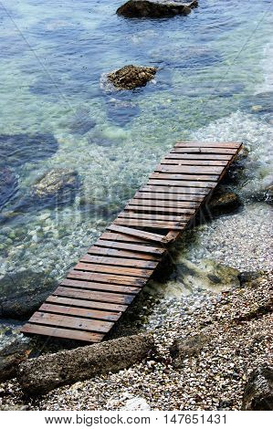 Wooden walkways on the pebbly clear seashore