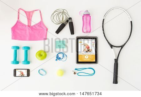 sport, fitness, healthy lifestyle, technology and objects concept - tablet pc computer with smartphone and sports stuff over white background