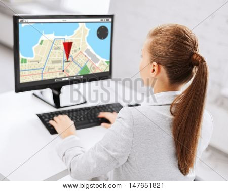 business, people, technology, navigation and education concept - businesswoman or student girl with gps navigator map on screen on computer screen sitting at office table