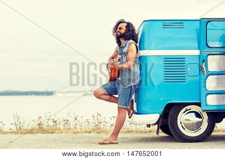 nature, summer, youth culture, music and people concept - young hippie man playing guitar and singing over minivan car on beach