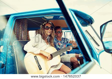 summer holidays, road trip, vacation, travel and people concept - smiling young hippie couple with guitar playing music in minivan car