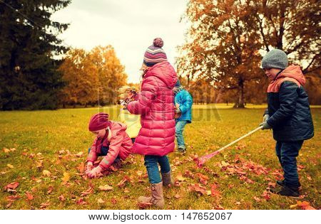 childhood, leisure, autumn, friendship and people concept - group of children with rack collecting and racking leaves in park