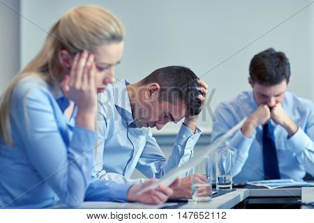 business, teamwork, people and crisis concept - business team sitting sad and solving problem in off