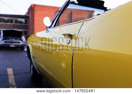 classic retro vintage yellow car. Autoshow background behind