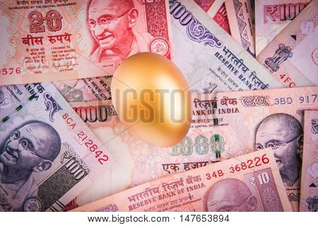 A gold egg lying on indian currency notes of 10, 20, 100, 1000 rupee value