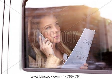 Portrait of a beautiful serious business woman advising on the phone about financial documents, analyzing important graphics, in the car on the way to work, active morning of a business people