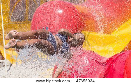 Happy girl having fun in water amusement park. , jumping and splashing in outdoors swimming pool in aquapark during summer sea vacation
