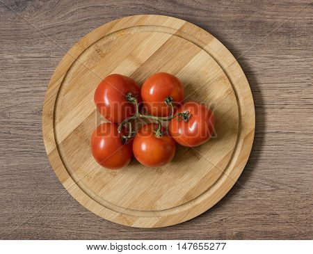Fresh raw food. Red tomato bunch on the bamboo cutting board. Brown wood imitating background