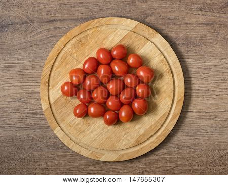 Fresh raw tomatos food. Red cherry tomatoes on the bamboo cutting board. Brown wood imitating background
