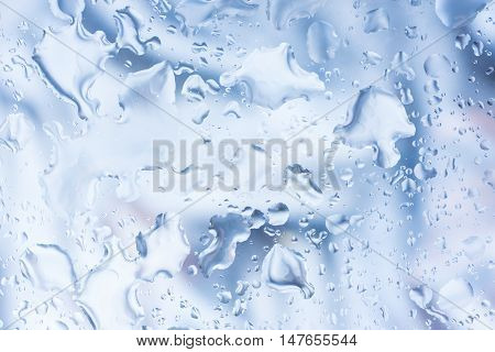 Rain droplets. Spilled water drops on glass natural blue background