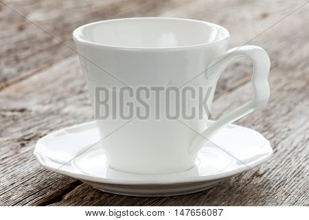 Empty coffee cup with plate on old wooden surface