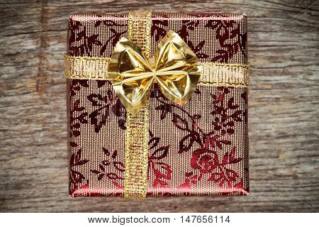 Gift box with golden bow. On old wooden background.