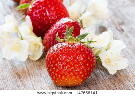 Red strawberries and wild flowers on wooden background