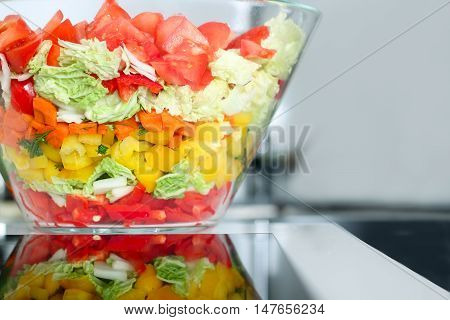 salad with vegetables and greens. Gray background behind.
