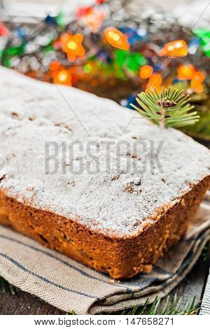 Cake With Raisins Sprinkled With Icing On A Wooden Table With Christmas Tree And Christmas Lights