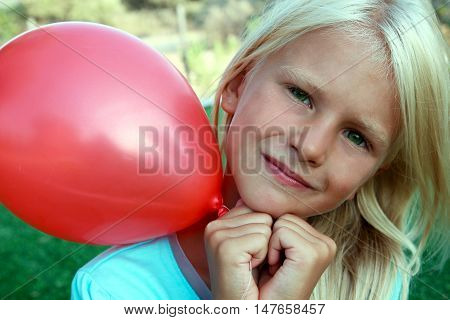 beautiful blonde girl siting on the grass and holding a red ball