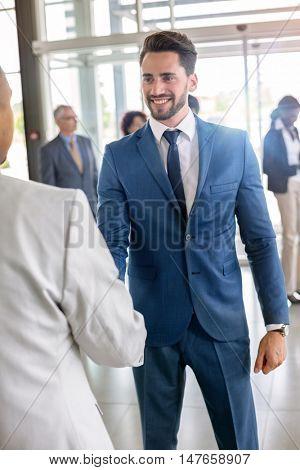 Enterprise officer at entrance heartily welcomes guest