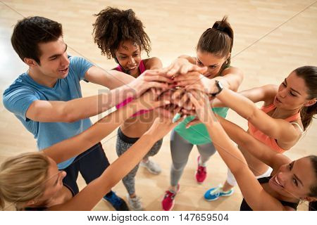 Group of fitness exercisers with hands over each other in gym