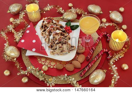 Christmas food still life with stollen cake slices, egg nog, holly, fir, gold bauble decorations,foil wrapped chocolates, candles, candy canes and almond nuts over red background.