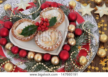 Traditional christmas mince pies in a heart shaped dish with red and gold bauble decorations, holly, snow covered winter greenery and stars.