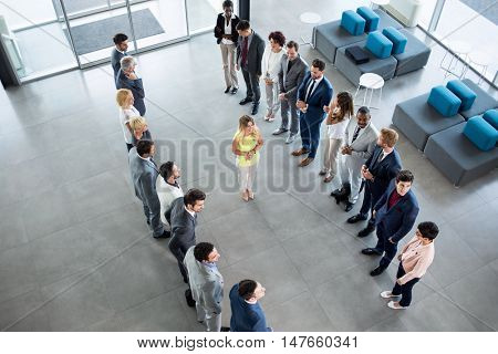 smiling young leader standing in front of his partners who applauding